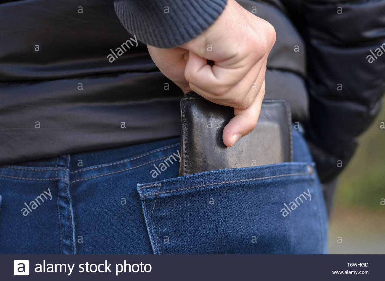 Pickpocket stealing a protruding purse - Stock Image