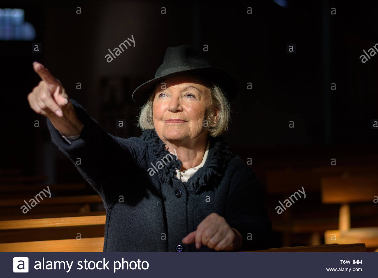 Bereaved elderly lady praying in a church - Stock Image