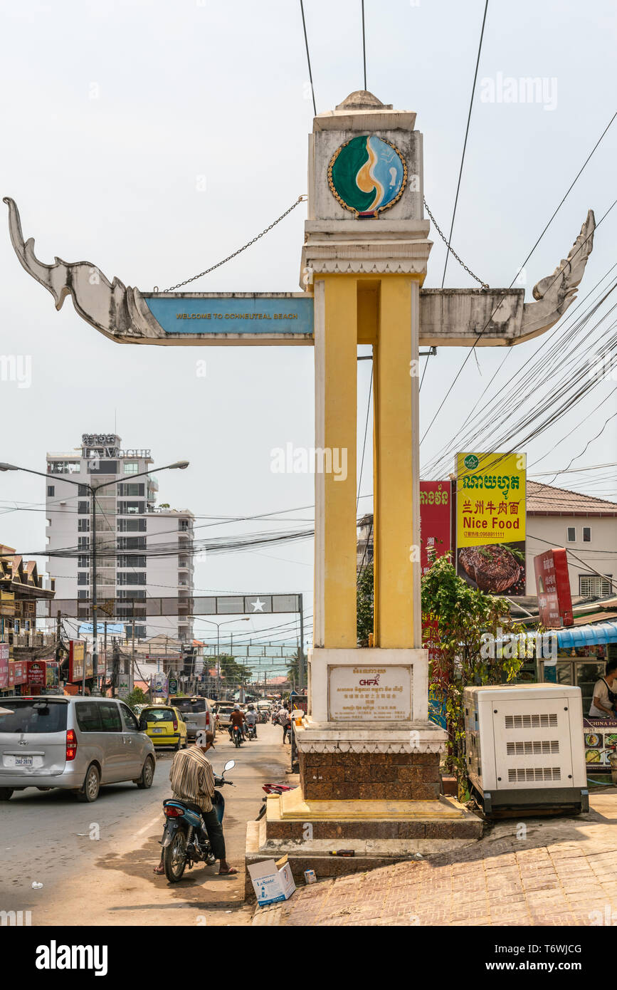 Sihanoukville, Cambodia - March 15, 2019: Culturally appropriate giant sign announcing Ochheuteal Beach neighborhood. Street scene with traffic and fo - Stock Image