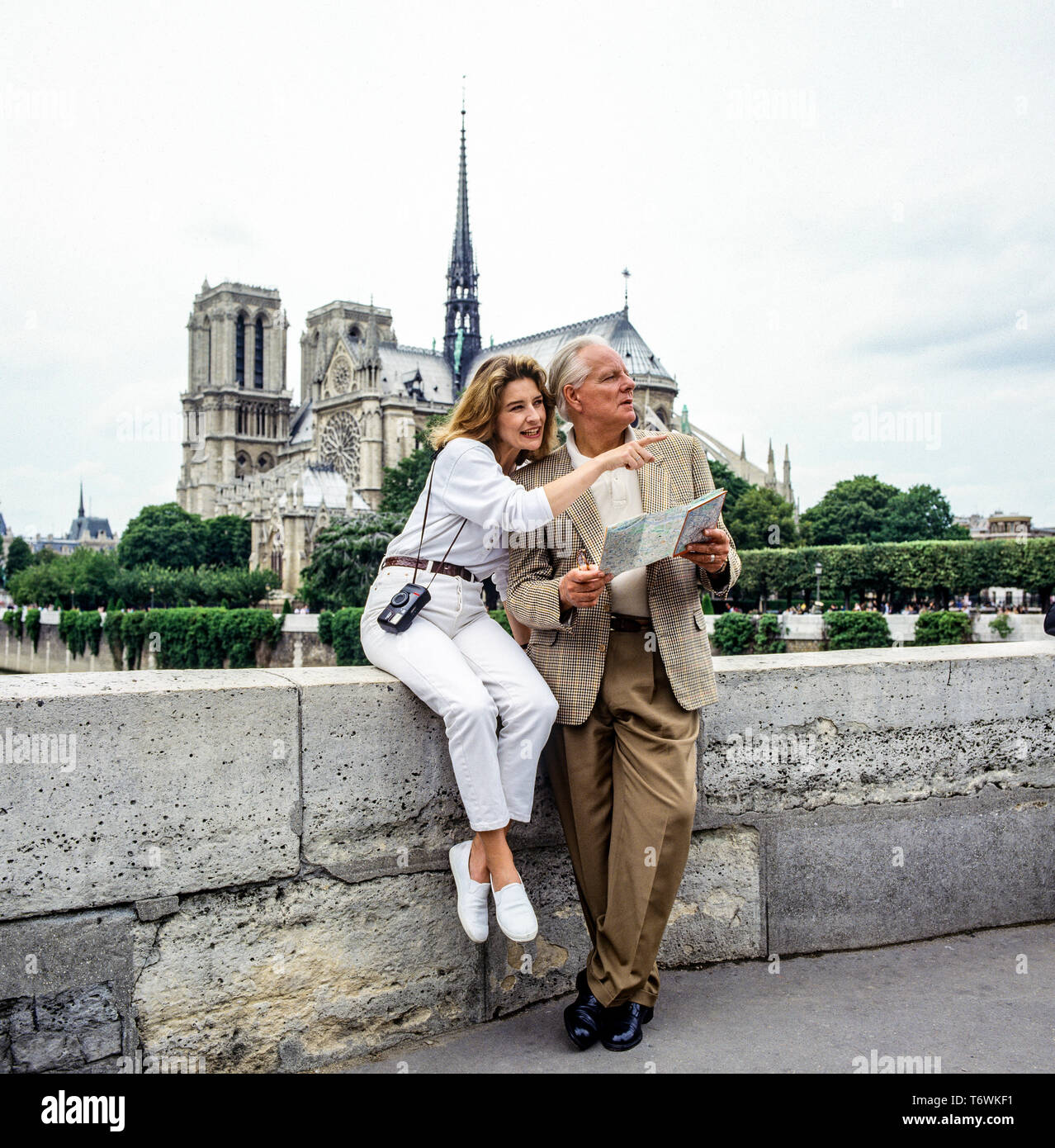 Couple of middle aged tourists looking at city map in front of Notre-Dame de Paris cathedral before the fire of April 15, 2019, Paris, France, Europe, Stock Photo
