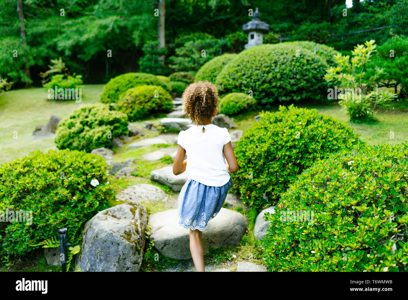 Rear view of a young girl walking down a path in a public park - Stock Image