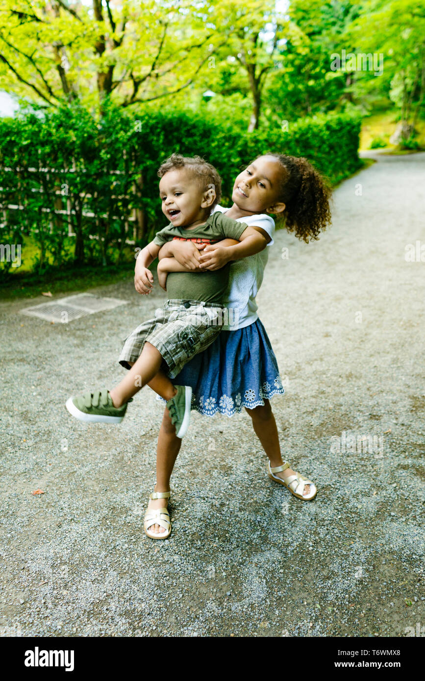 A young girl carries her little brother Stock Photo