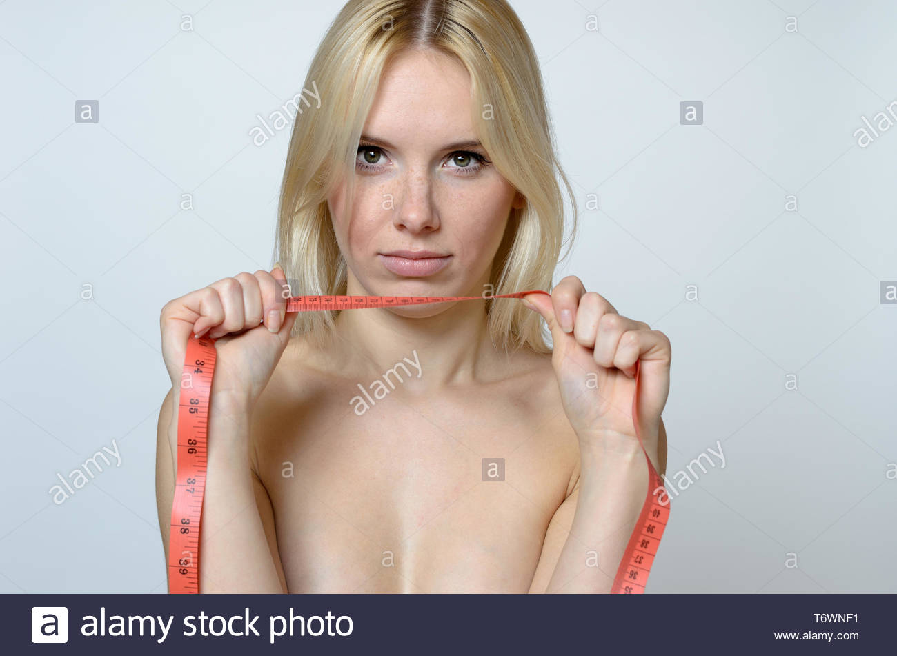 Bare Young Woman holding a Measuring Tape Stock Photo