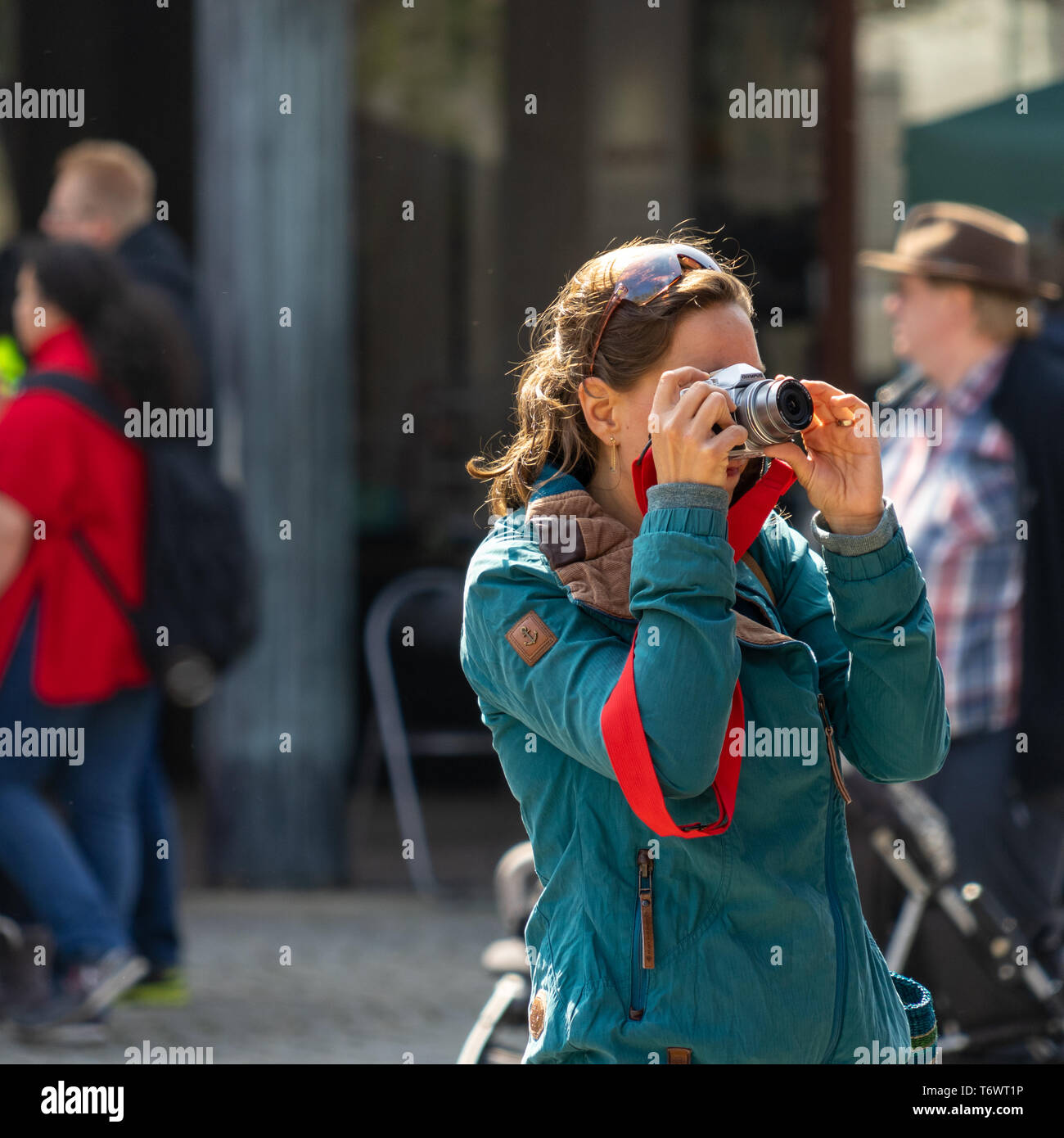 Wolfsburg, Germany, May 1, 2019: Young woman in a turquoise anorak taking photos with the camera - Stock Image