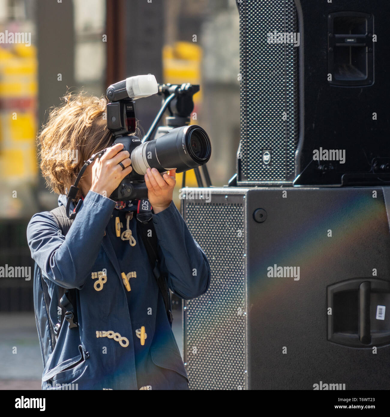 Wolfsburg, Germany, May 1, 2019: Young woman in a blue anorak taking photos with the camera - Stock Image