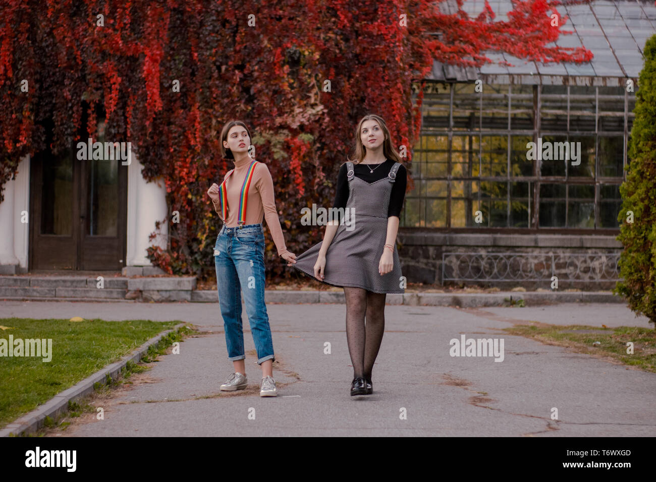Two beautiful students walking in the autumn park - Stock Image