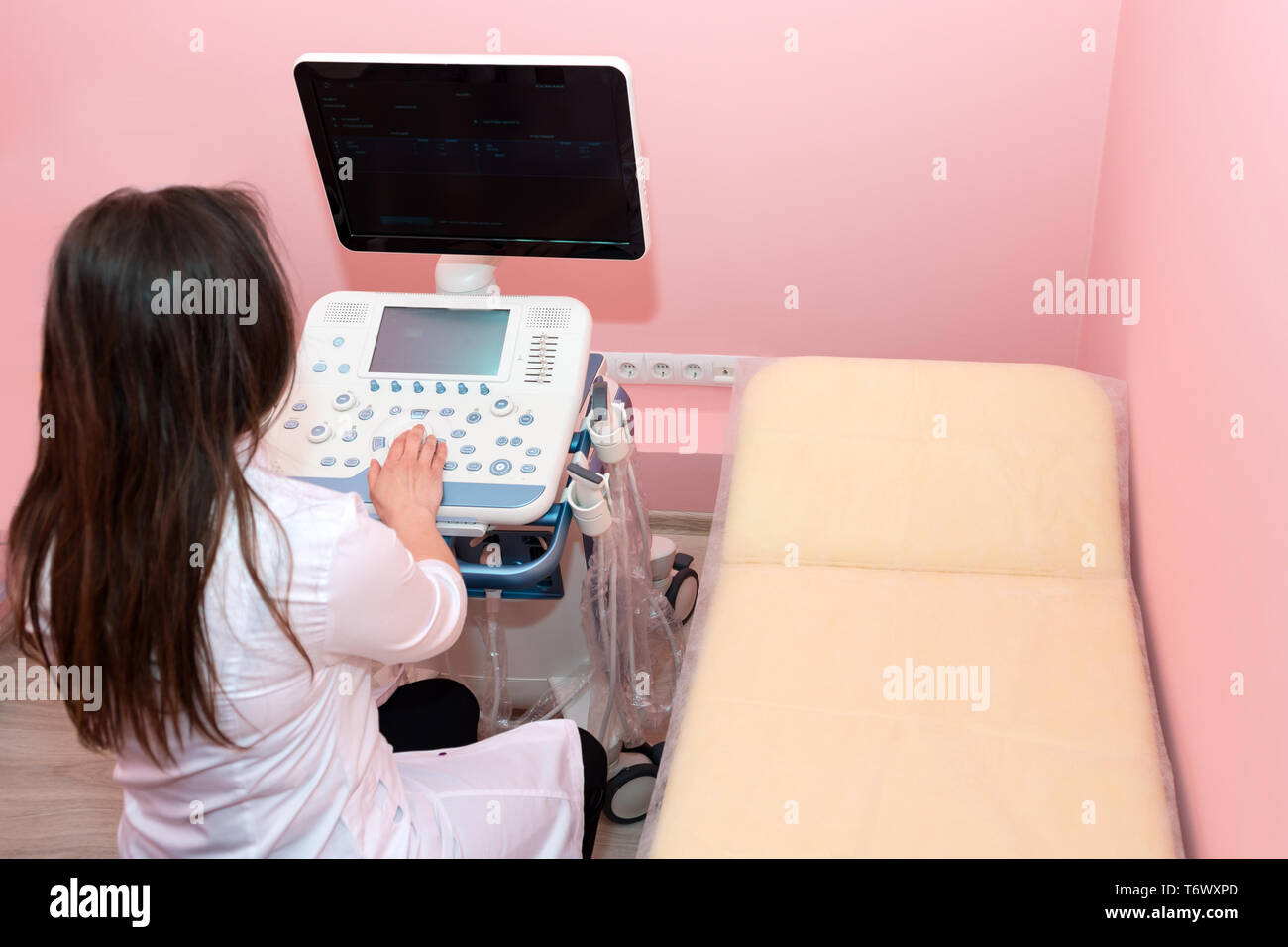 Doctor performing ultrasound scan in clinic. Expecting of child and diagnosing with ultrasound. - Stock Image