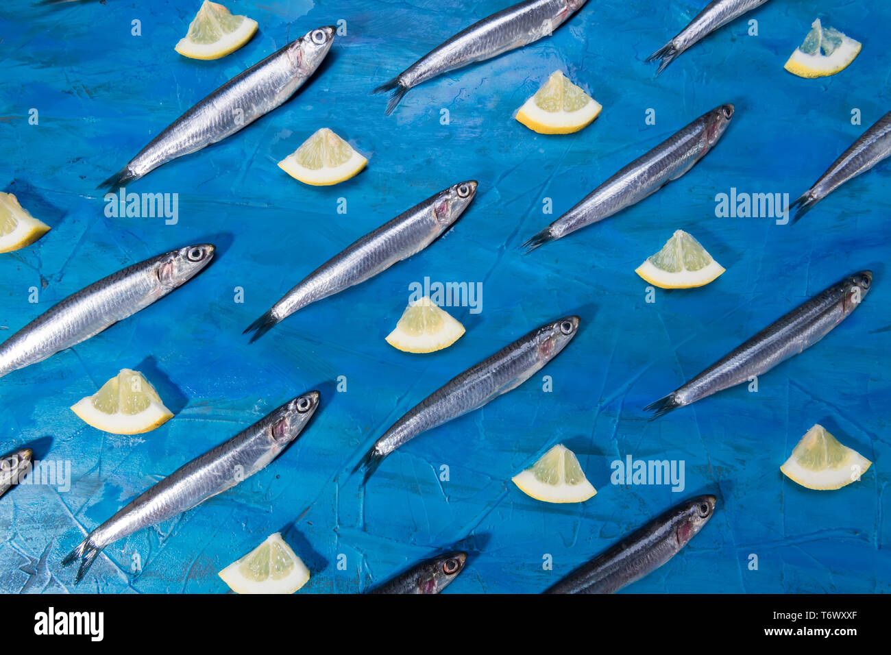 Fish pattern. Anchovies with slice of lemon on a black stone on a blue sea background. Fish caught in the Ionian Sea - Stock Image