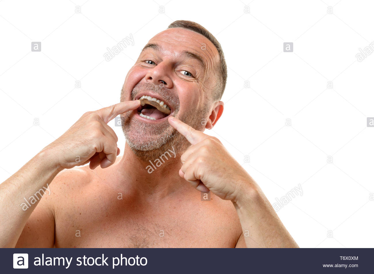 Bare chested man points to teeth with two fingers - Stock Image