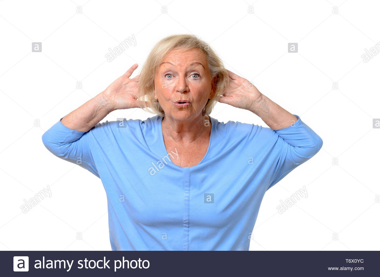 Wide-eyed senior woman with hands behind head - Stock Image