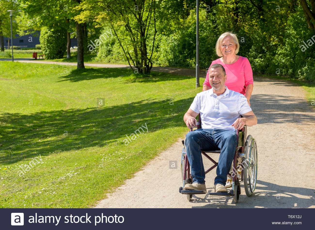Man seated in wheel chair while wife pushes Stock Photo