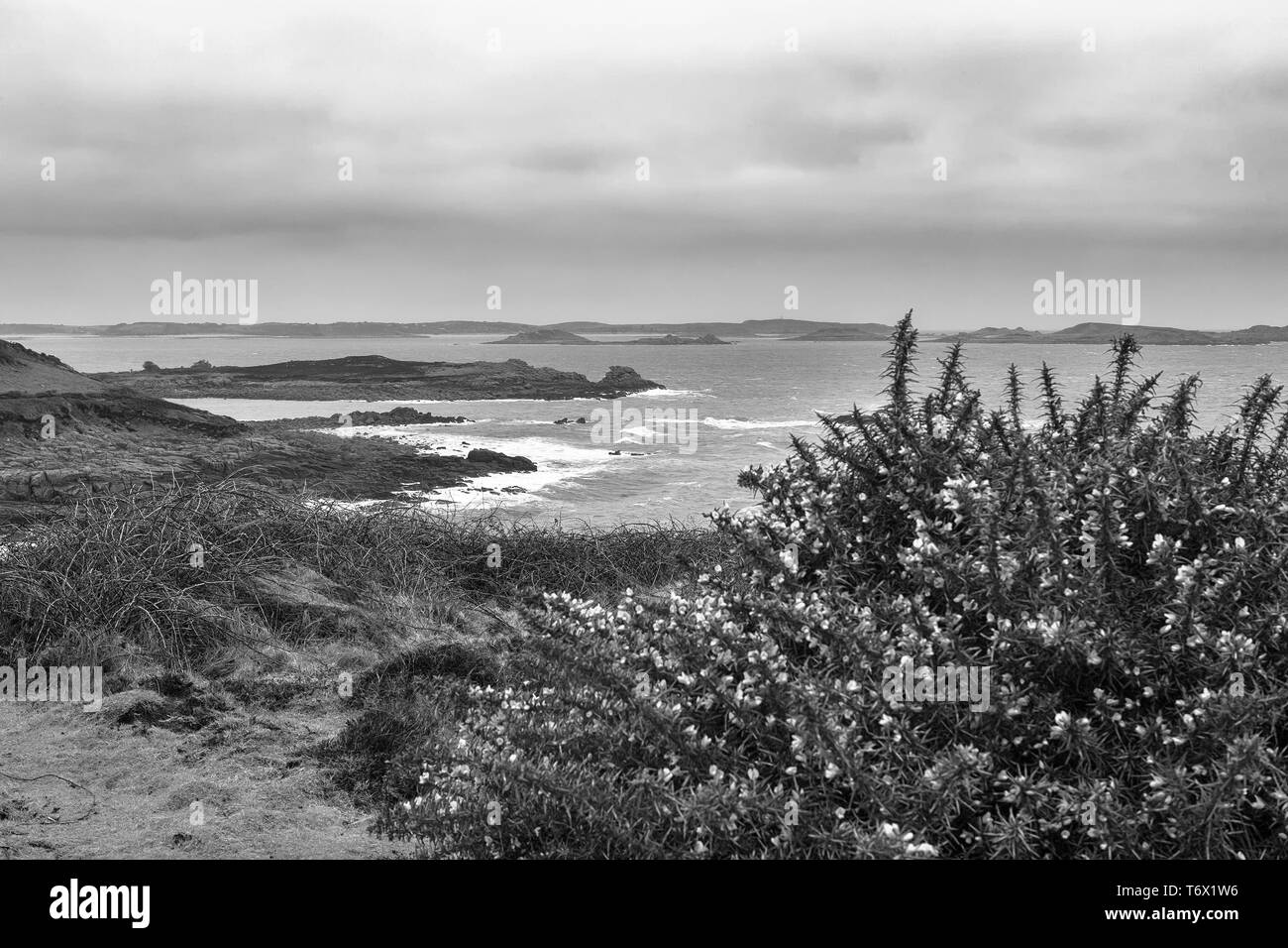 View across Crow Sound to the Eastern Isles from Gap Point, St. Mary's, Isles of Scilly, UK on a windy and overcast day: black and white version - Stock Image