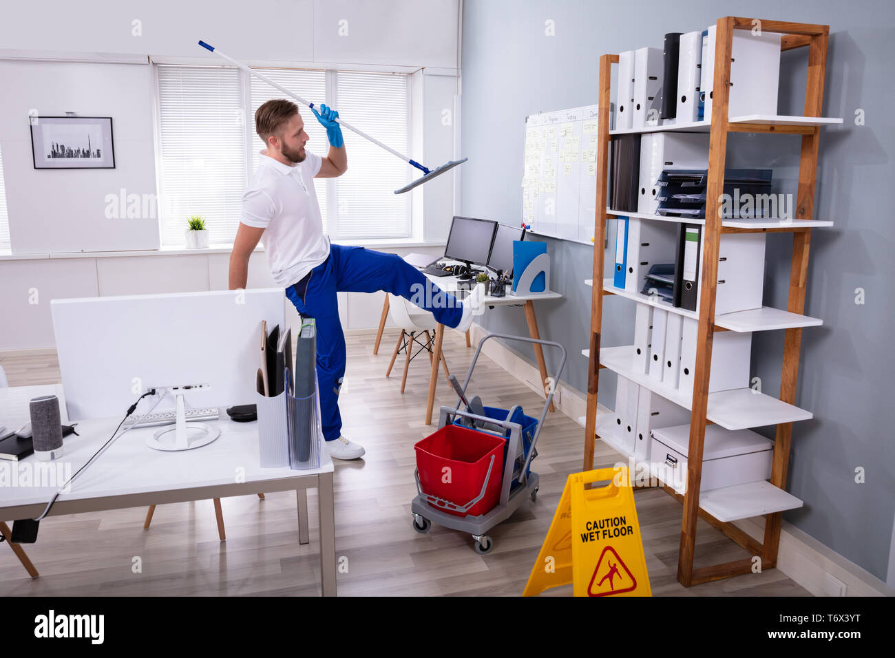 Man Janitor Slipping While Mopping Floor In Modern Office - Stock Image