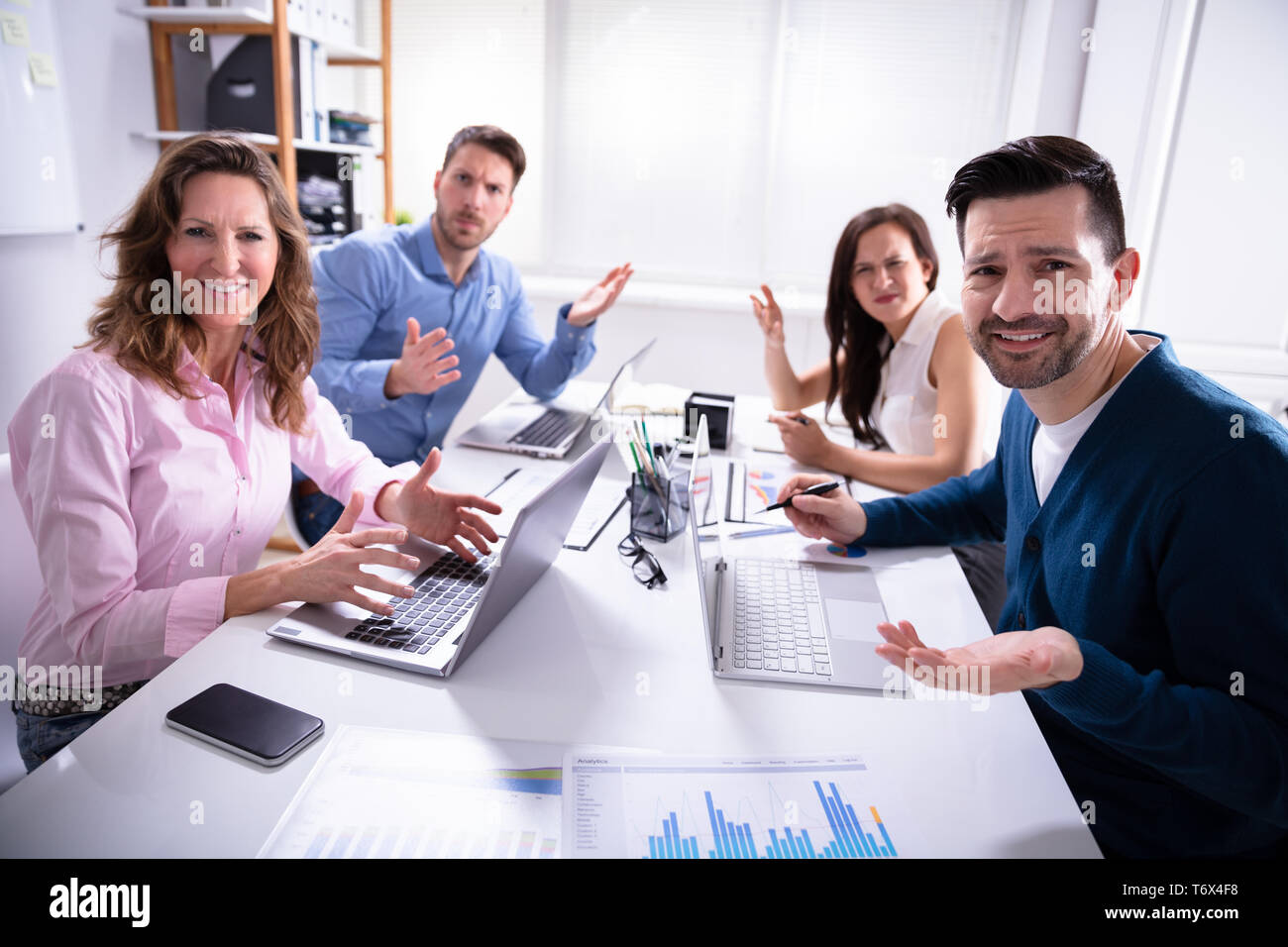 Group Of Business Executives Complaining Toward Camera In Office - Stock Image