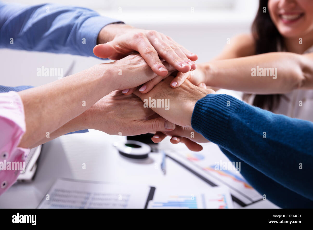 Group Of Businesspeople Stacking Hands Over Desk In Office - Stock Image