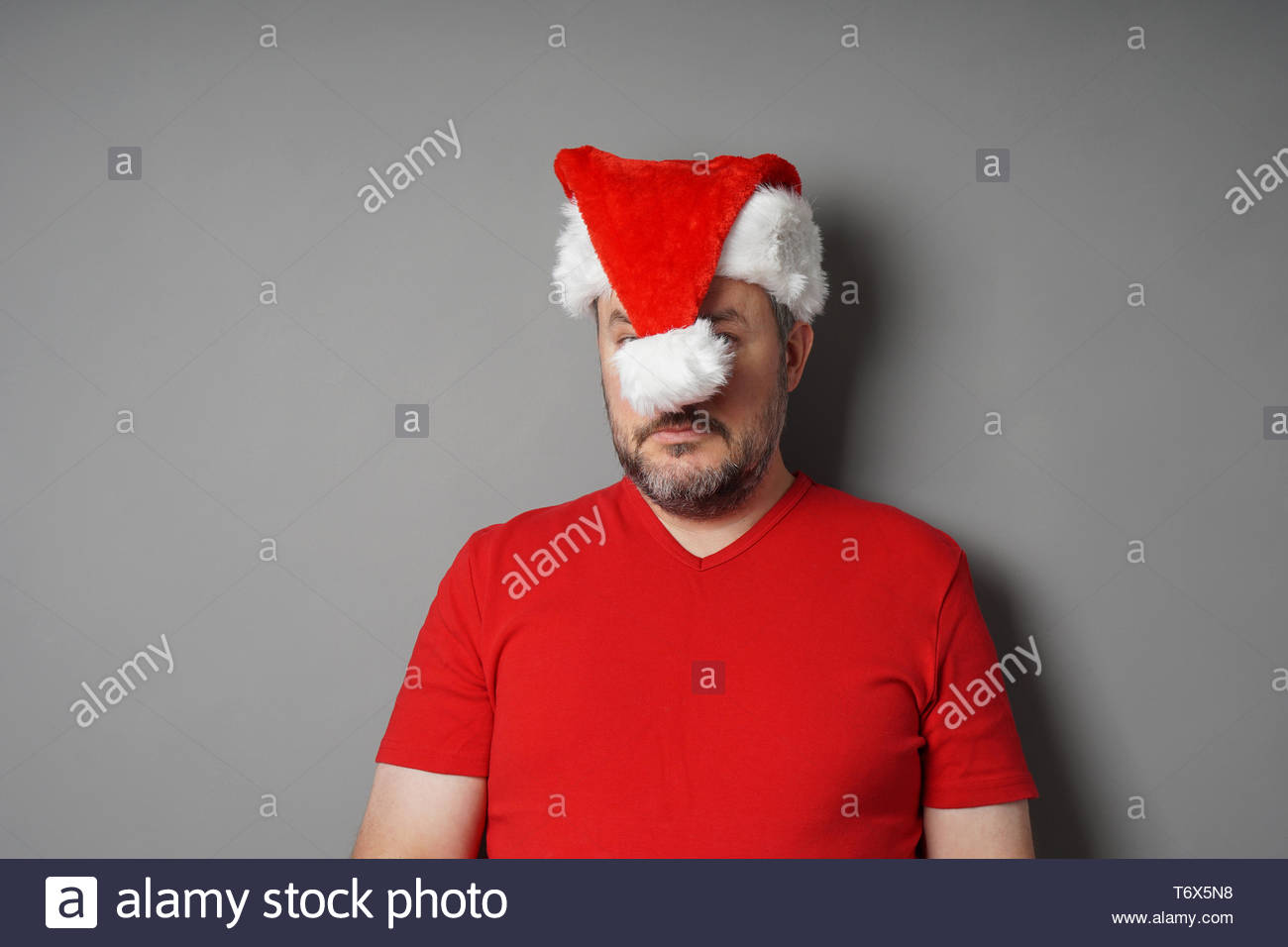 Christmas Hater.Christmas Hater Hiding Face Behind Santa Hat Stock Photo