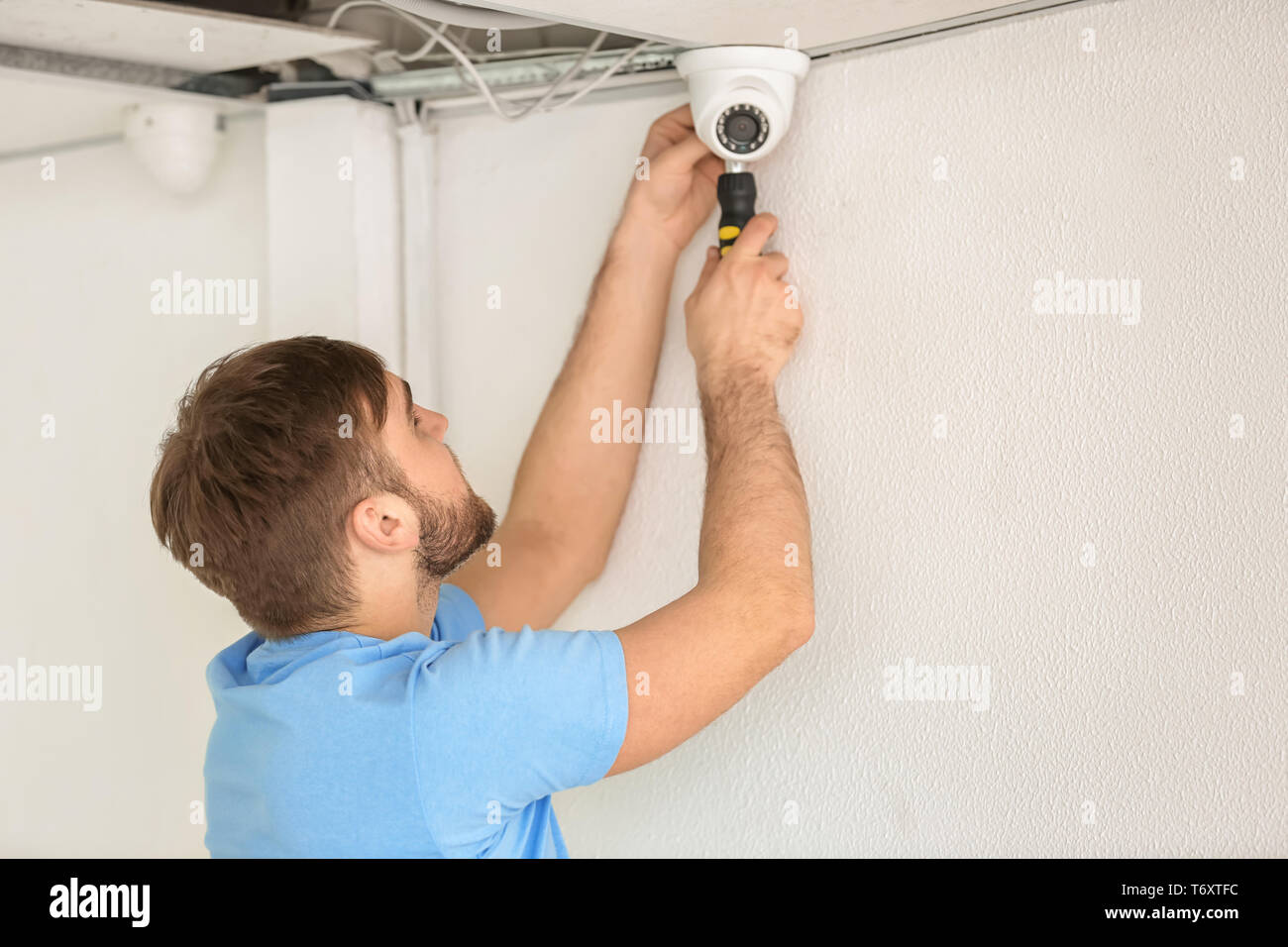 Electrician installing security camera indoors Stock Photo ... on security camera supports, security camera mounting parts, security camera building, security camera fittings, security camera painting, security camera junction boxes, security camera adapters, security camera cables, security camera schematics, security camera bulbs, security camera conduit, security camera mounting base, security camera filter, security camera features, security camera voltage, security camera software, security camera pinout, security camera furniture, security camera components, security camera sensor,