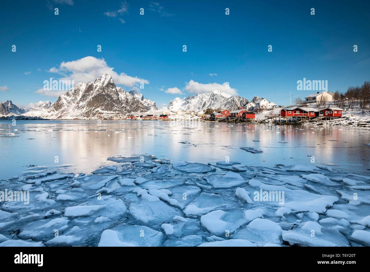 Cabins by the fjord with ice floes in the foreground, fishing village Reine, Olstinden, Moskenesoya, Lofoten, Norway - Stock Image