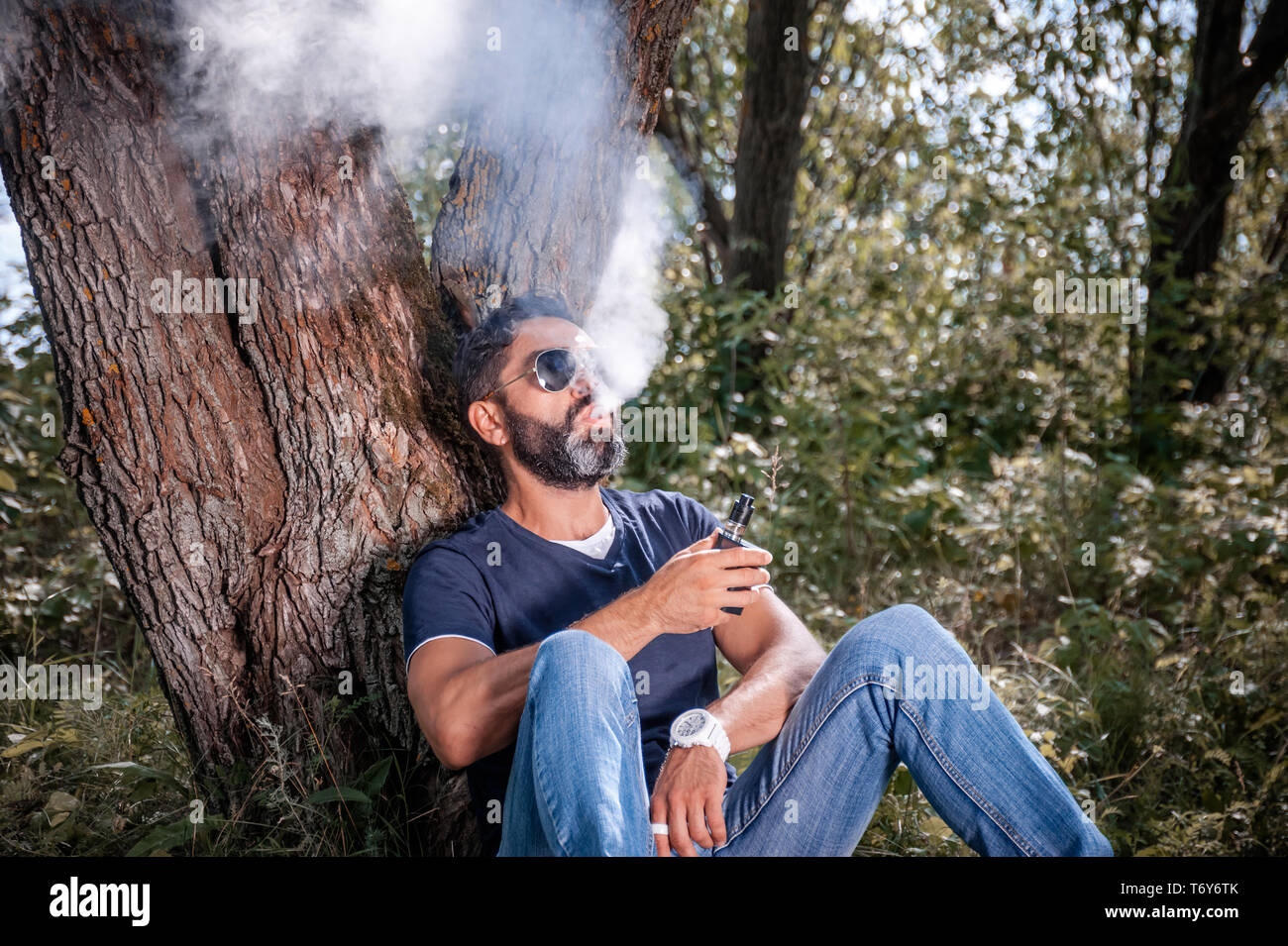 Brutal smoker blows up a couple an electronic cigarette on the ground. Electronic cigarette concept. - Stock Image