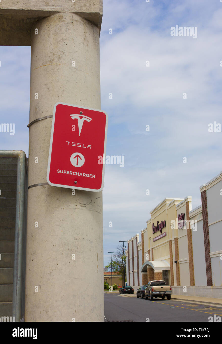 """In May 2019, it was announced that Tesla, Inc. co-founder/CEO Elon Musk was one of the winners of the 2019 Stephen Hawking Medal for Science Communication. Pictured in April 2019, in vertical orientation and with various stores in the background at the Towne Centre at Laurel shopping center/centre in Laurel, Maryland, USA, a red """"Tesla Supercharger"""" sign with logo on a pillar of the parking garage/multi-storey car park where charging stations are available for the California-based automotive company's electric vehicles. As of May 2019, Tesla had more than 1,440 Supercharger stations worldwide. Stock Photo"""