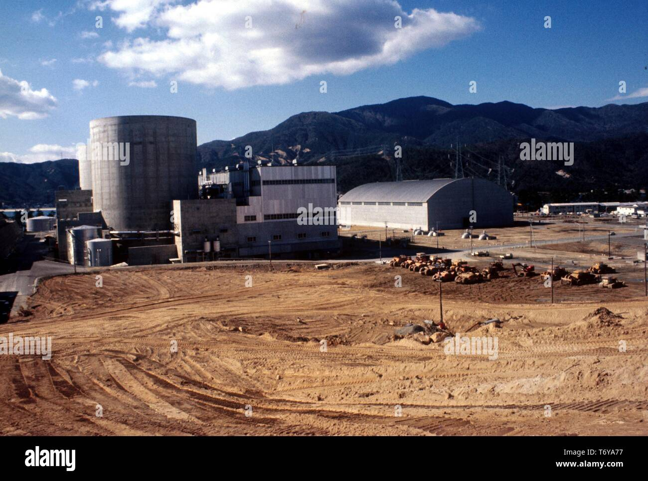 The exterior of Mihama Nuclear Power Plant, on a sunny day, with dirt and construction vehicles in the foreground, Mihama, Japan, 1975. Image courtesy US Department of Energy. () - Stock Image