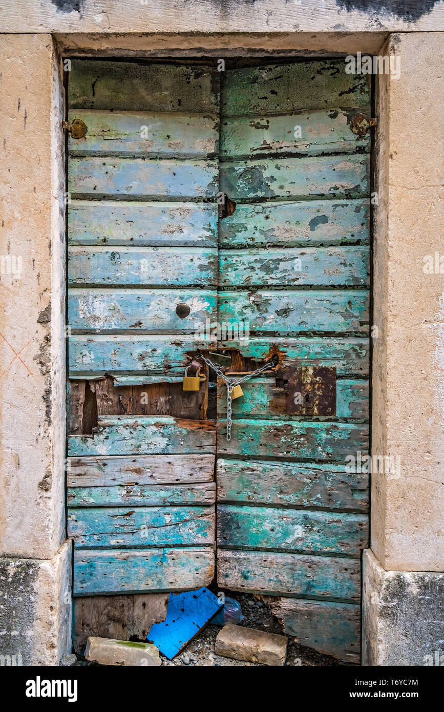 Locked old green damaged wooden doors Stock Photo