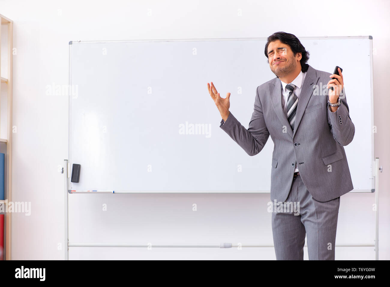 Young handsome businessman standing in front of whiteboard - Stock Image