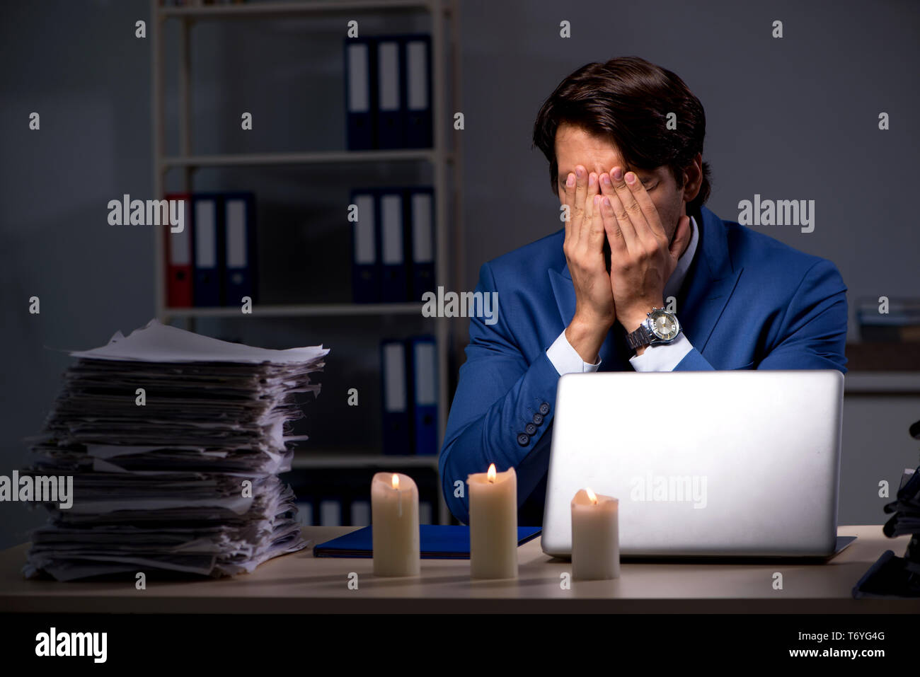 Businessman working late in office with candle light - Stock Image
