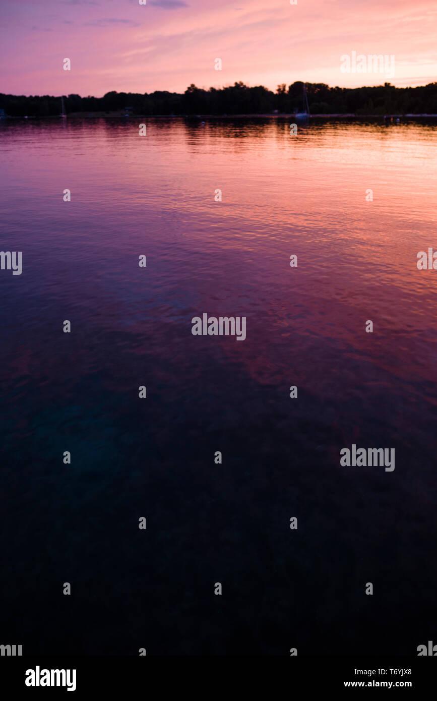 Dramatic sunset reflecting on surface of Lake Michigan Stock Photo
