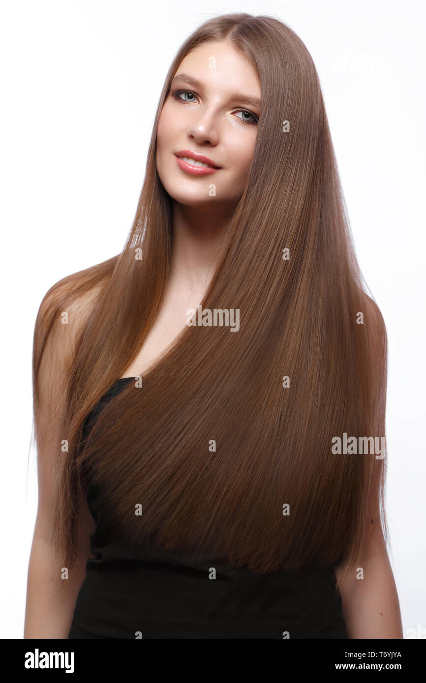Beautiful brown-haired girl in move with a perfectly smooth hair, and classic make-up. - Stock Image
