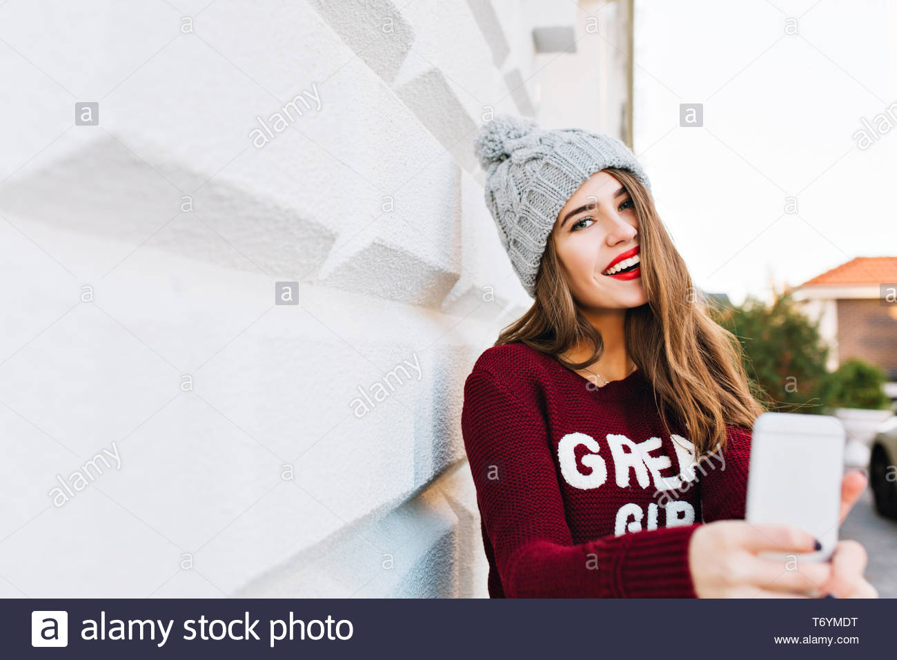 6c521928d717f3 Portrait pretty girl with long hair in marsala sweater making selfie on  grey wall background.