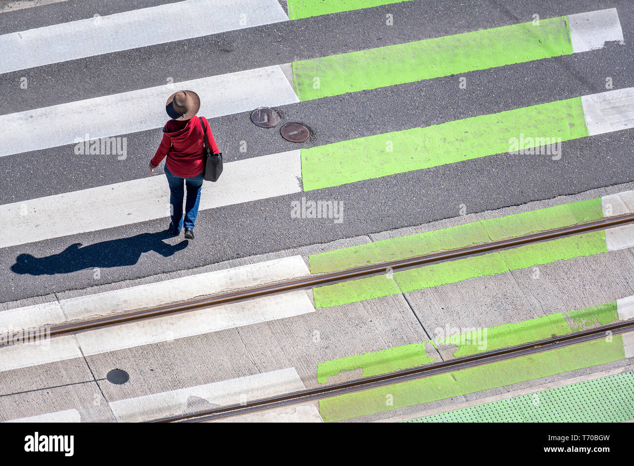 Elegant slender woman in a hat, red cardigan and jeans crosses the road on a zebra pedestrian crossing observing the rules of the road to protect your - Stock Image