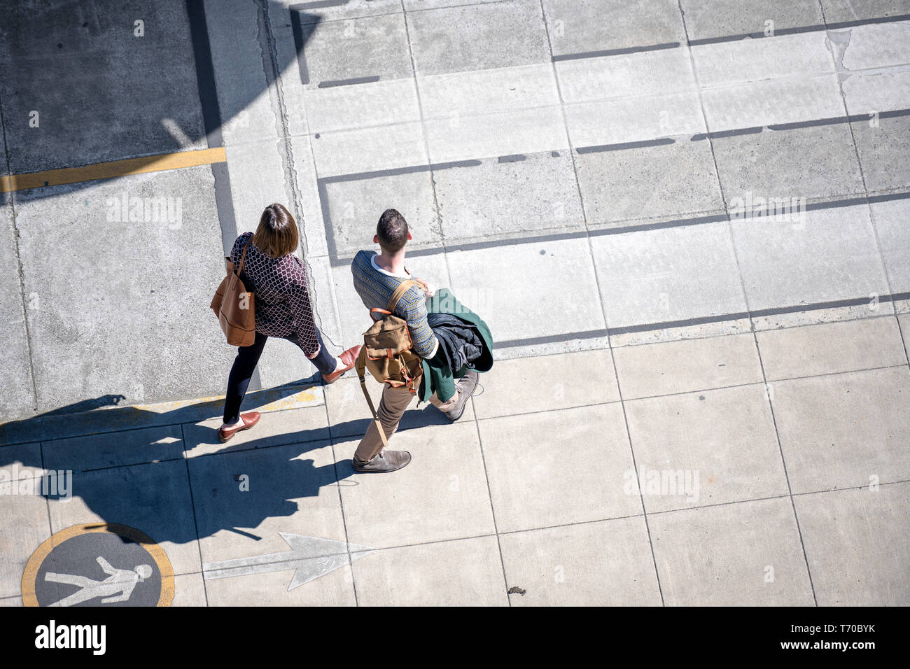 Couple a man with backpack and a woman with bag are confidently walking along the footpath with markings on the sidewalk preferring to move actively t - Stock Image