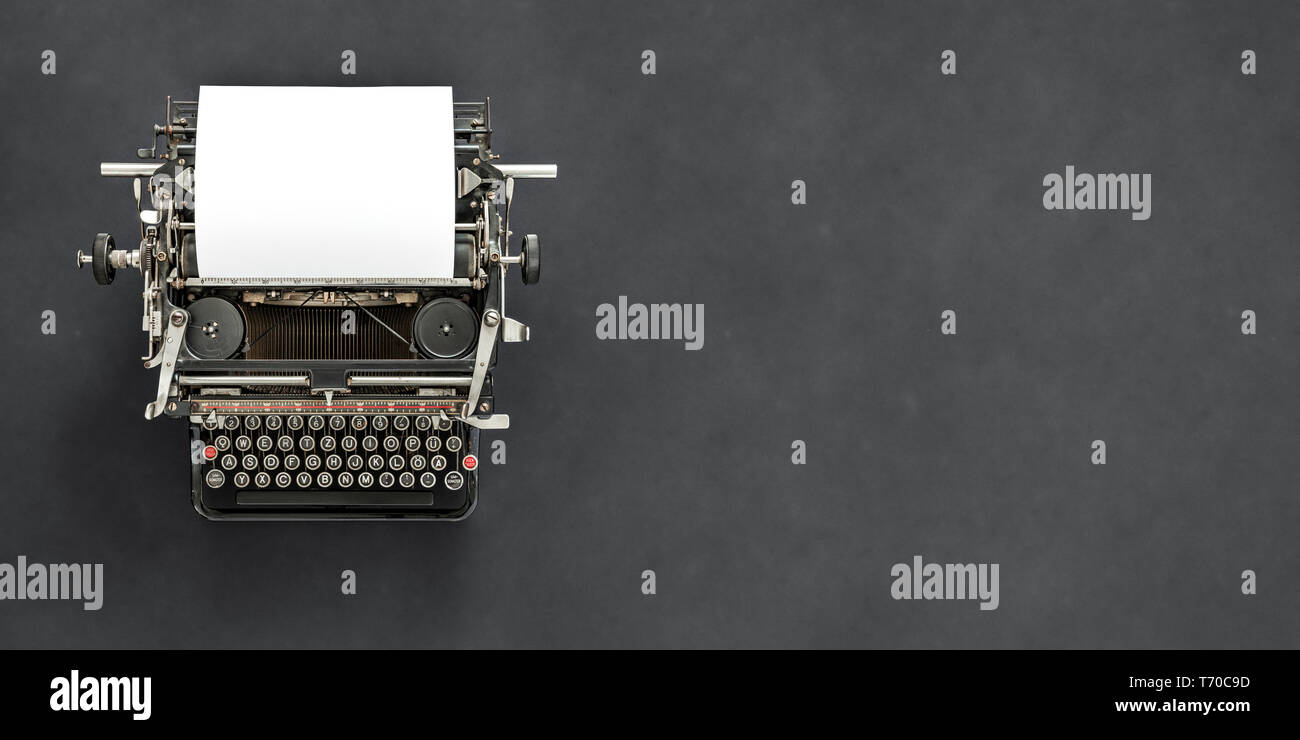 Vintage typewriter with blank sheet of paper retro technology Stock Photo