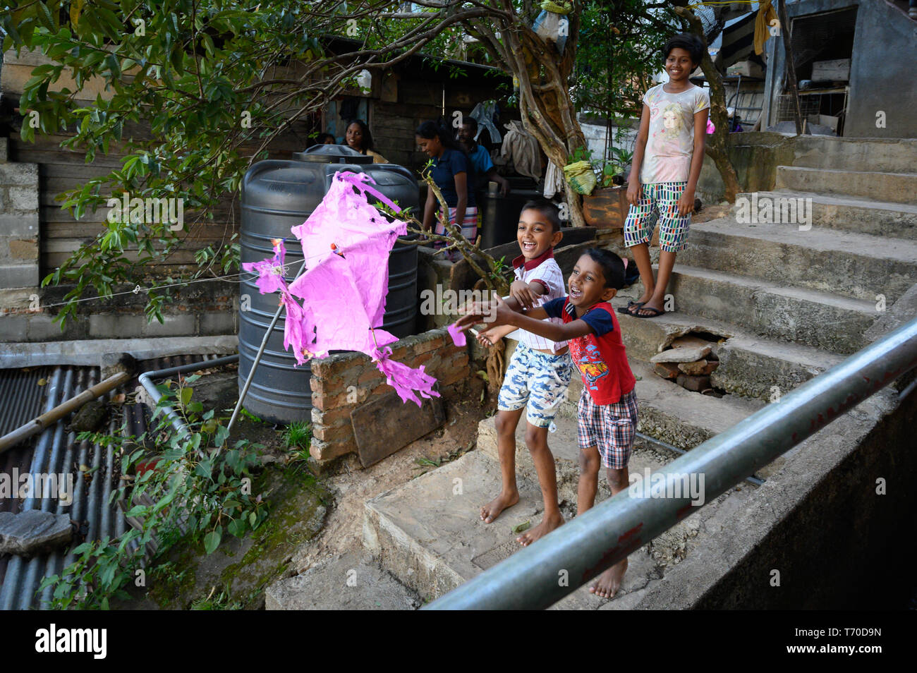 Children flying a kite in a residential area of Kandy, Sri Lanka - Stock Image