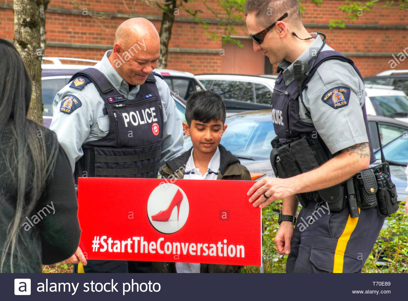 RCMP officers and  pre-teen male holding a red sign with an image of a red high heeled shoe reading #StartTheConversation for gender equality. - Stock Image