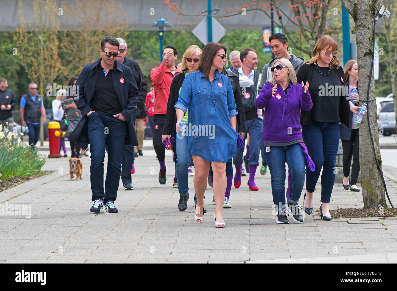 A group of people walking for gender equality during a Walk a Mile in Her Shoes campaign. - Stock Image