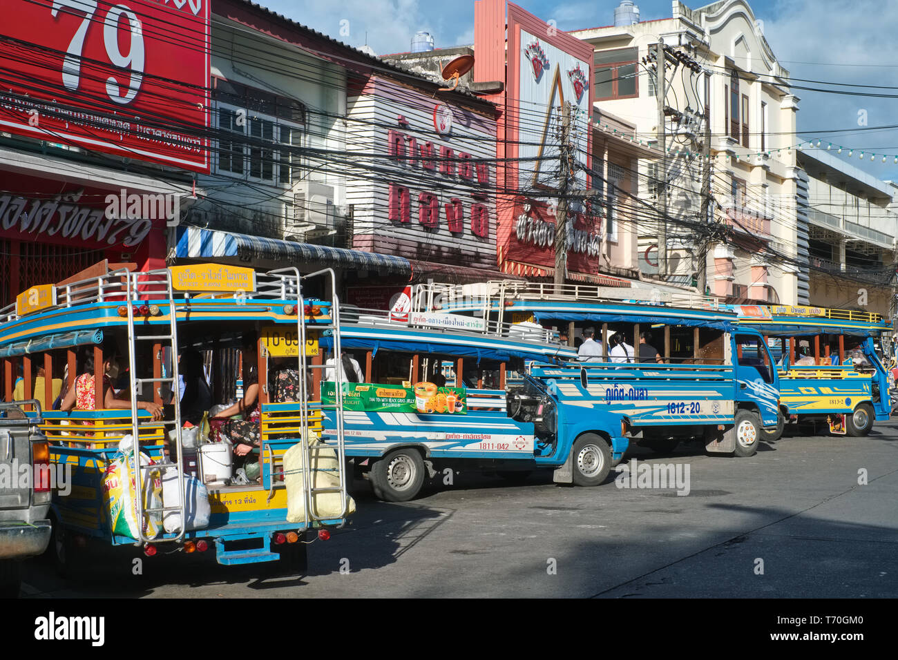 Quaint local buses called Songthaews at a bus stop in Ranong Rd., Phuket Town, Thailand, connecting the town with the island's beaches - Stock Image