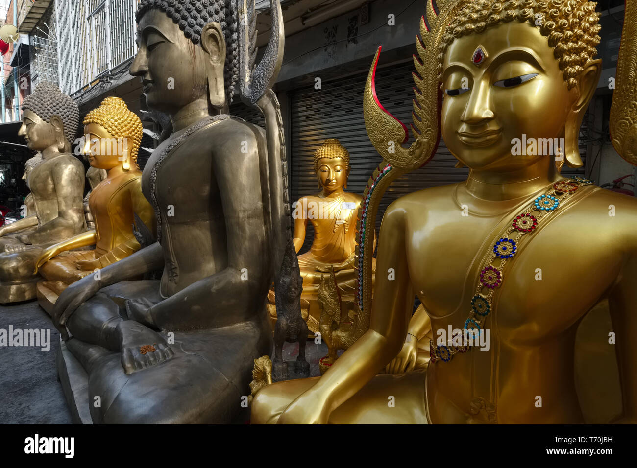 Buddha statues outside a factory for religious objects in Bamrung Muang Road, Bangkok, Thailand - Stock Image