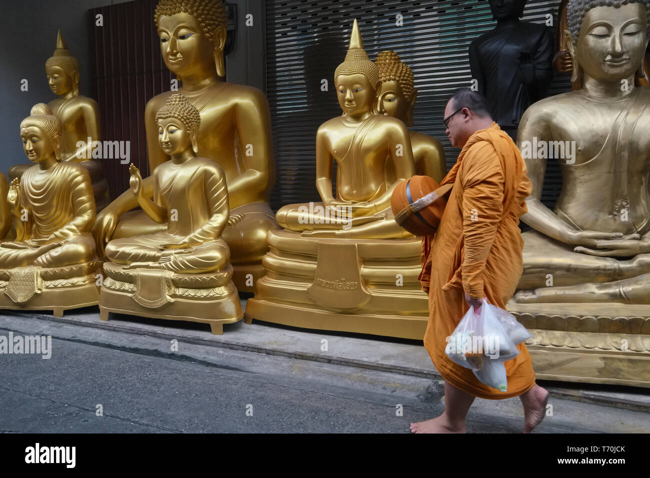 A Buddhist monk passes Buddha statues outside a factory for religious objects in Bamrung Muang Road, Bangkok, Thailand, ready for delivery - Stock Image