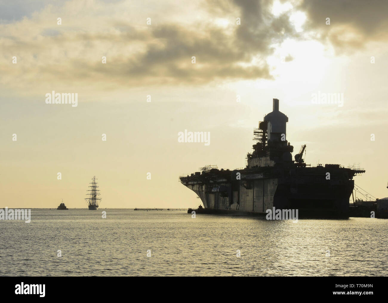 """190430-N-ED185-1011  MAYPORT, Fla. (April 30, 2019) The Brazilian navy tall ship Cisne Branco, left, appears on the horizon as it enters Naval Station (NAVSTA) Mayport. Cisne Branco, which means """"white swan,"""" is a sail training tall ship operated by the Brazilian navy. Cisne Branco is visiting NAVSTA Mayport for a port visit as part of the ship's EUROPA 2019 tour. (U.S. Navy photo by Mass Communication Specialist 1st Class Brian G. Reynolds/Released) - Stock Image"""