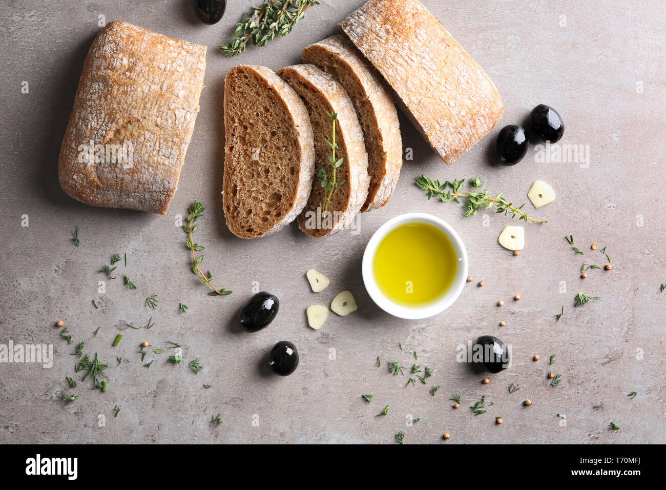 Bowl with oil, black olives and bread on grey background, top view Stock Photo