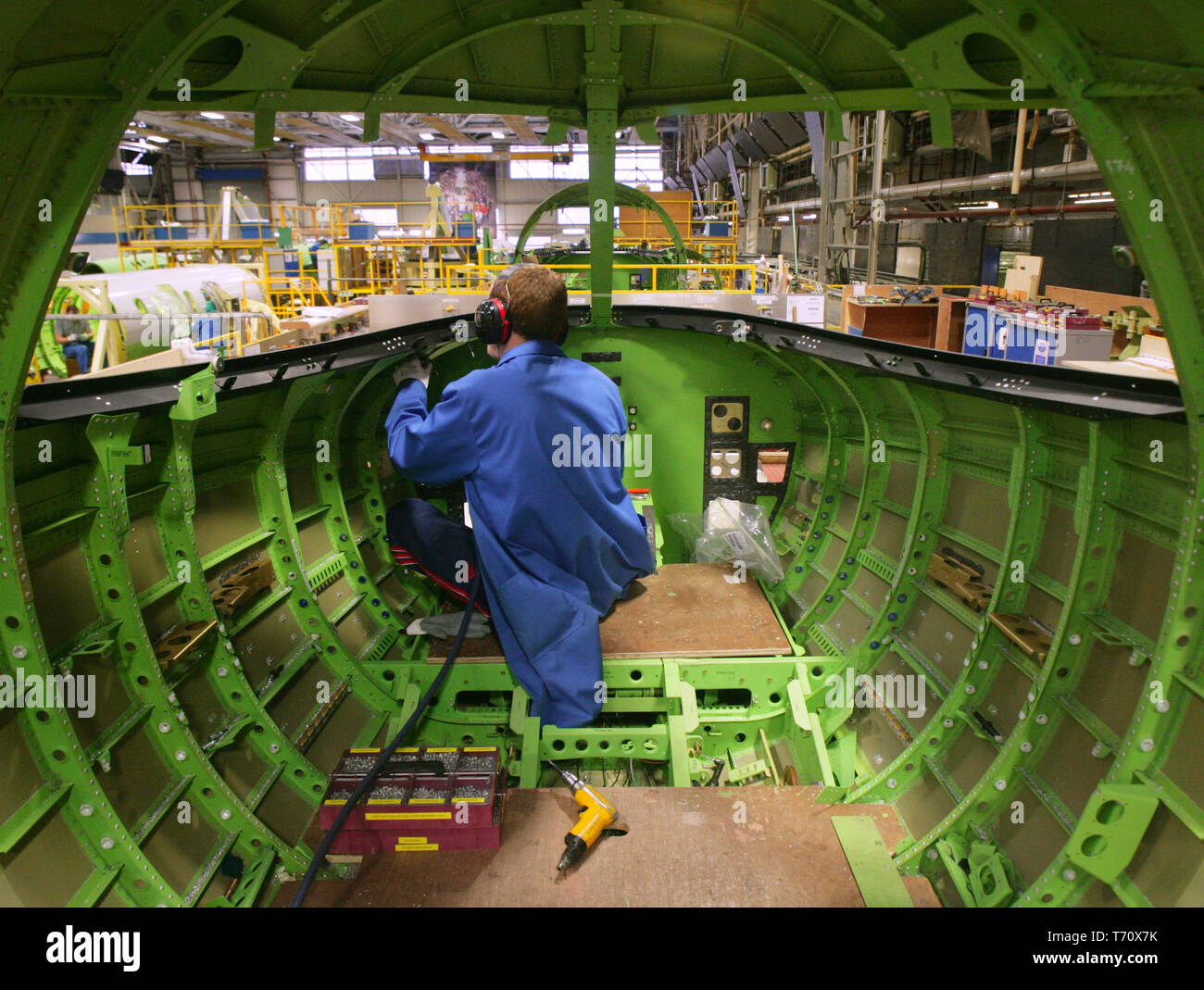 """FILE PHOTO - Bombardier aircraft electricians work on Learjet 40 XR aircraft on the production line in Belfast, Northern Ireland, on Monday, Jan. 21, 2008. Almost 1,000 jobs are to go at Bombardier Aerospace factories in Northern Ireland, Thursday, April 2, 2009. A total of 975 staff are losing their jobs, with 310 permanent staff and all 665 agency staff being made redundant. A company statement said it was cutting aircraft production rates and reducing manpower at all its sites because of an """"unprecedented recession"""".  Paul McErlane Photography Stock Photo"""