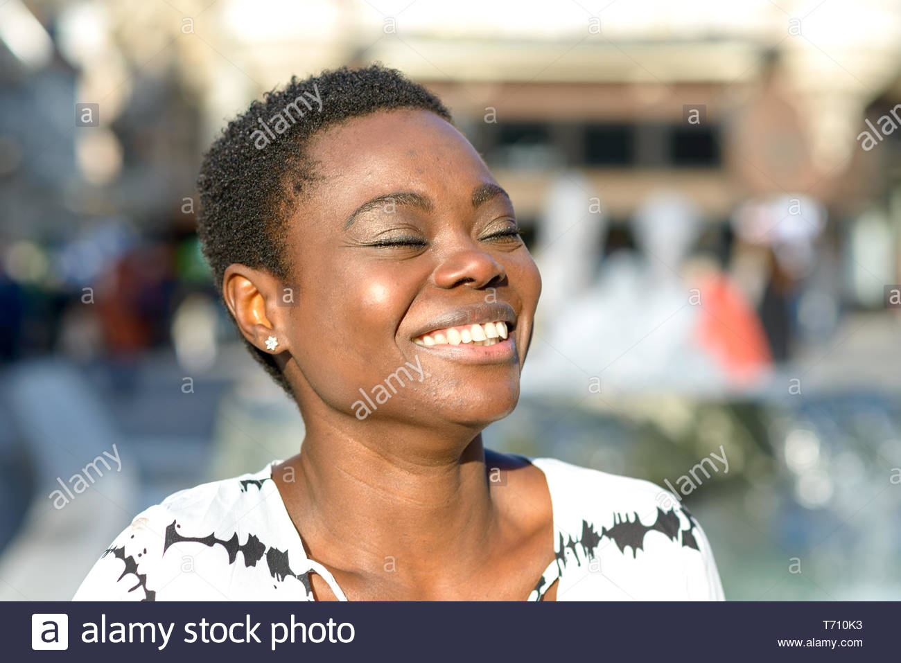 Lively young African woman with a beaming smile - Stock Image