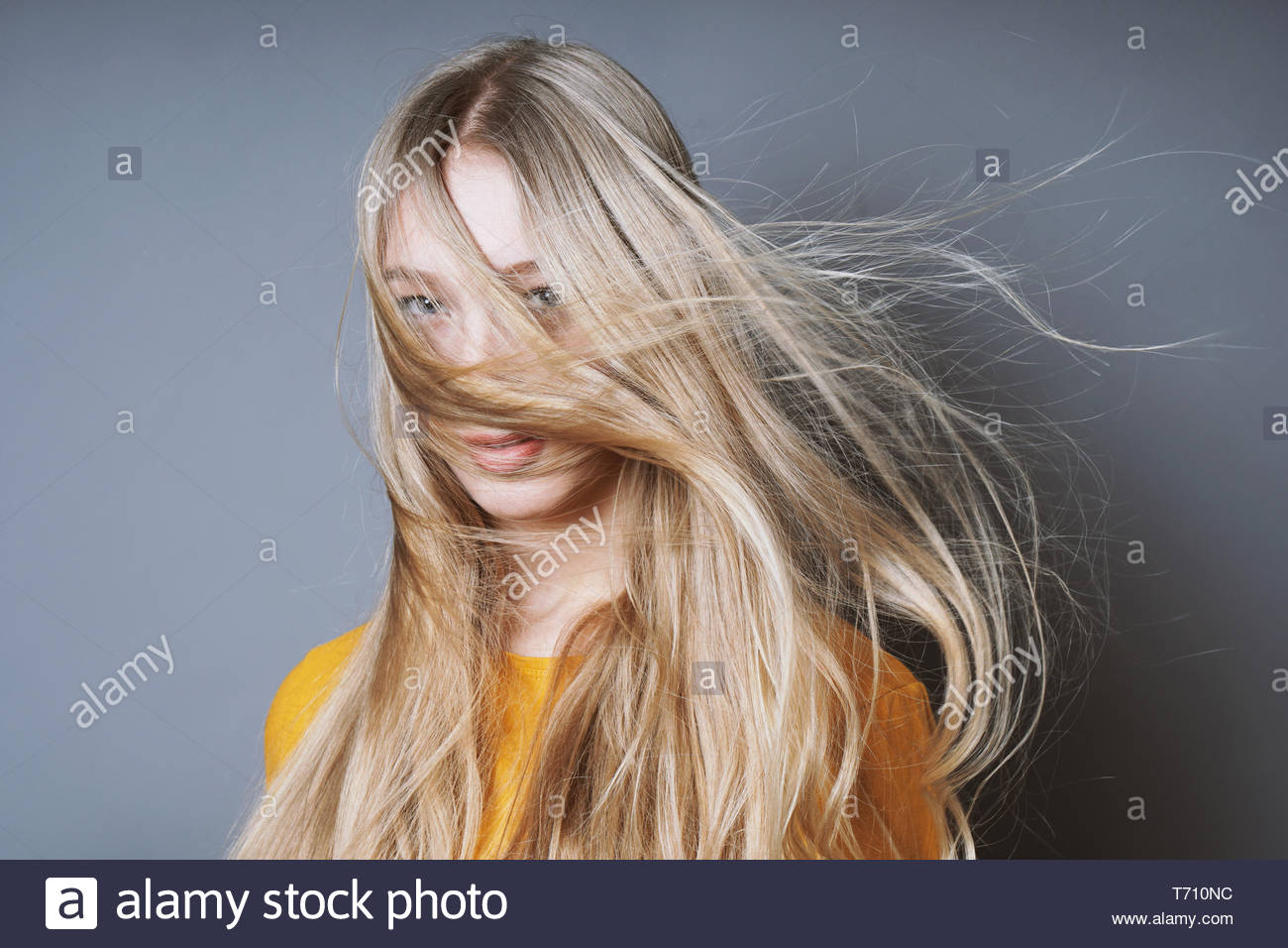 blond woman with long windswept tousled hair - Stock Image