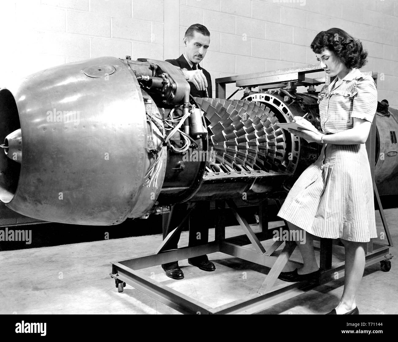 NASA employees inspecting the JUMO 004 Jet Engine with the cover removed at the Aircraft Engine Research Laboratory of the National Advisory Committee for Aeronautics (NACA), Cleveland, Ohio, March 24, 1946. Image courtesy National Aeronautics and Space Administration (NASA). () - Stock Image