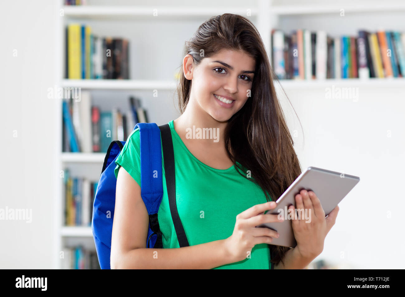 Mexican female student working with tablet computer at library of university - Stock Image