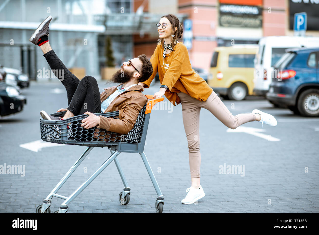 Young stylish coupe having fun riding with shopping cart on the outdoor parking near the supermarket Stock Photo