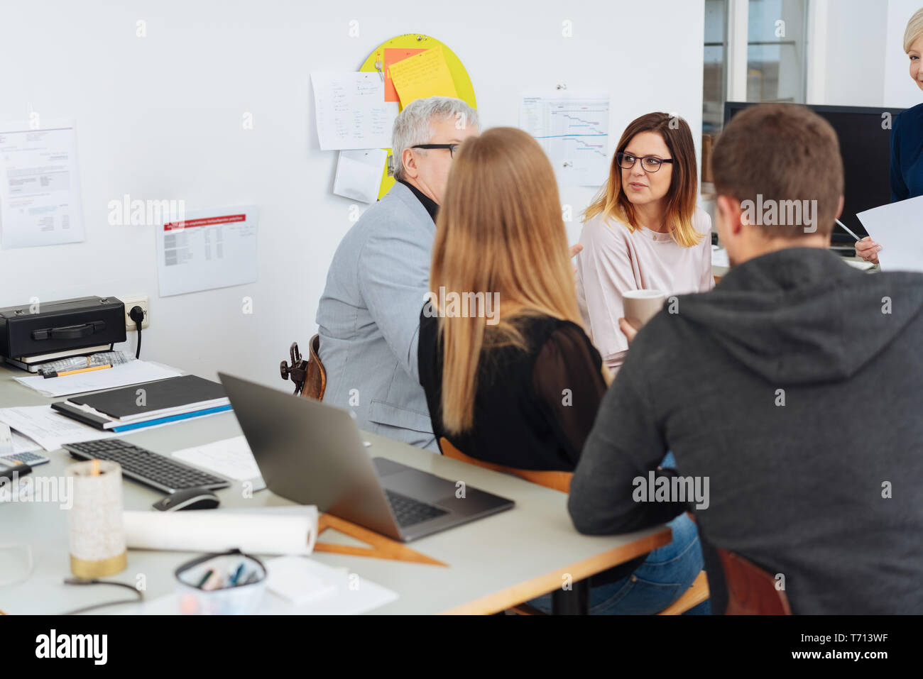 Co-workers in a brainstorming session at the office sitting around in a circle having a discussion with a view over a desk to a woman in the back of t - Stock Image