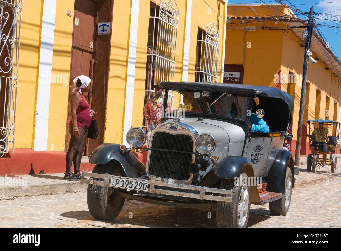 Colourful Classic American taxi driving along one of the cobblestone streets in colonial town of Trinidad,  Cuba, Caribbean - Stock Image